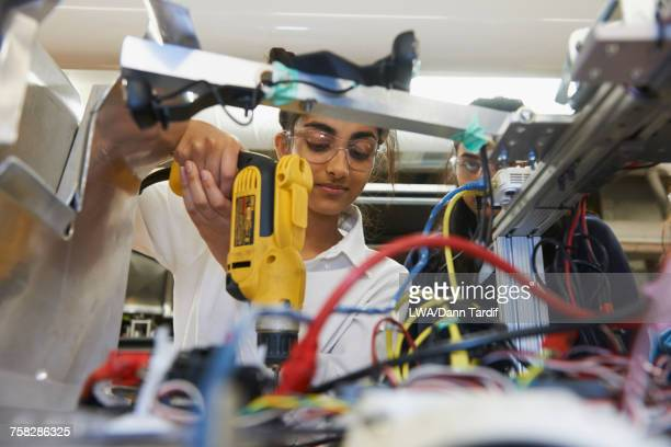 Girl in school using drill in engineering workshop