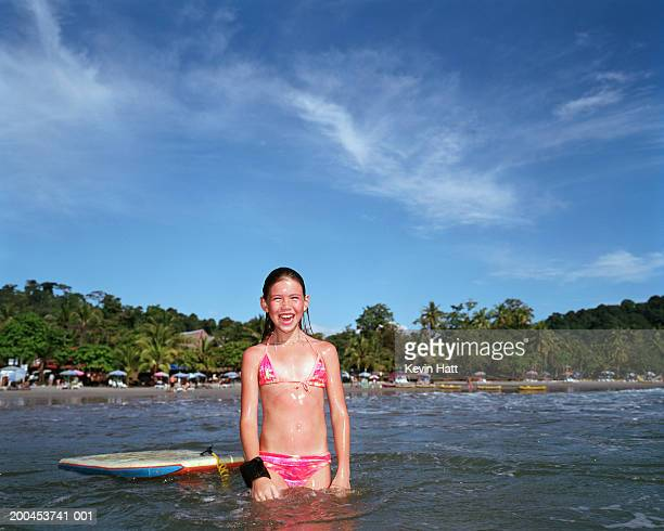 Girl (8-10) in sea with body board, smiling, portrait