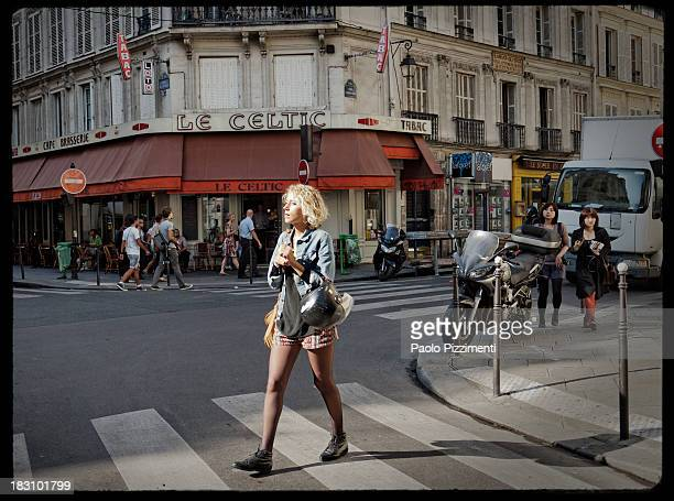 Girl in shorts walking into a Paris district