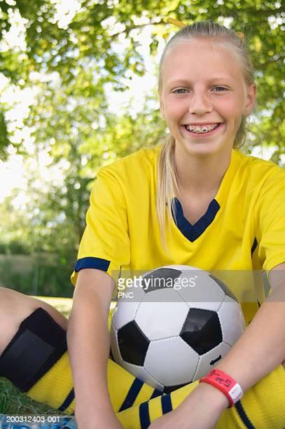 Girl (10-12) in soccer uniform sitting on field, smiling, portrait