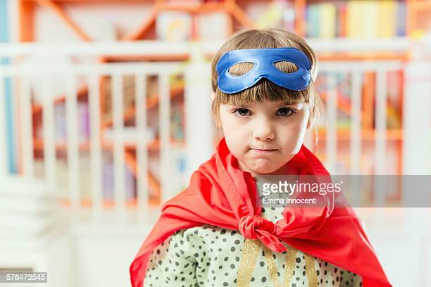 girl in spotty jumper with superhero mask and cape
