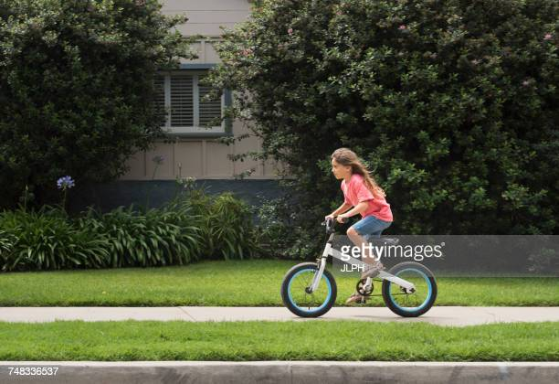 Girl in street cycling on bicycle