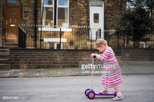 Girl in striped dress on scooter