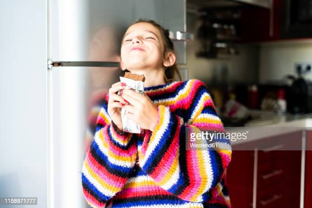 girl in striped pullover in kitchen at home eating chocolate - chocolate bar stock pictures, royalty-free photos & images