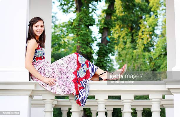 Girl in summer dress sitting on white balcony