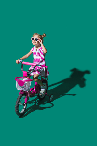 Girl in sunglasses bike riding against green background - gettyimageskorea