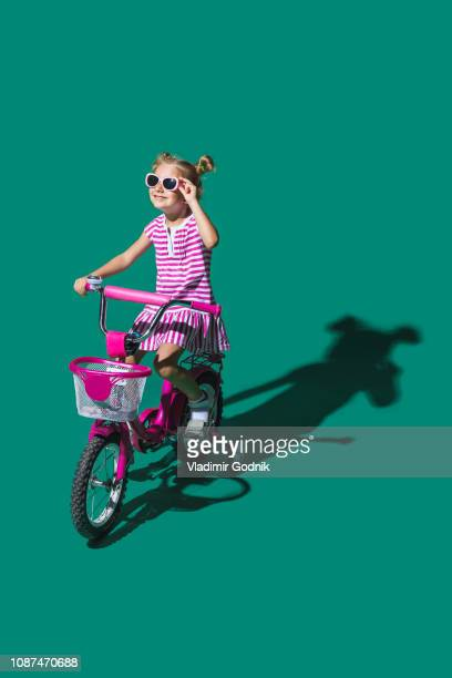 girl in sunglasses bike riding against green background - green dress stock pictures, royalty-free photos & images