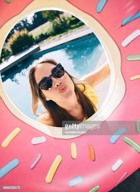 Mädchen in Sonnenbrille Rahmen mit rosa donut aufblasbaren pool
