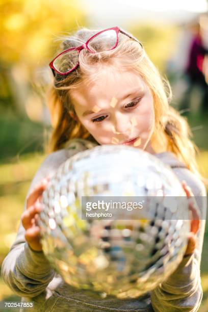 girl in sunlit garden gazing at disco ball - heshphoto stock pictures, royalty-free photos & images
