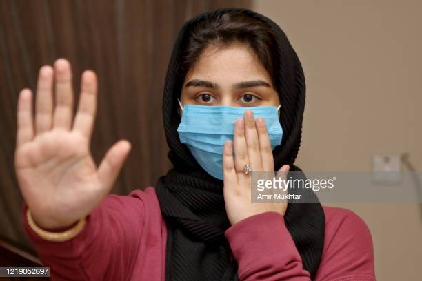 a girl in surgical face mask stopping or asking for social distancing for coronavirus (covid-19) protection. - pakistan stock pictures, royalty-free photos & images