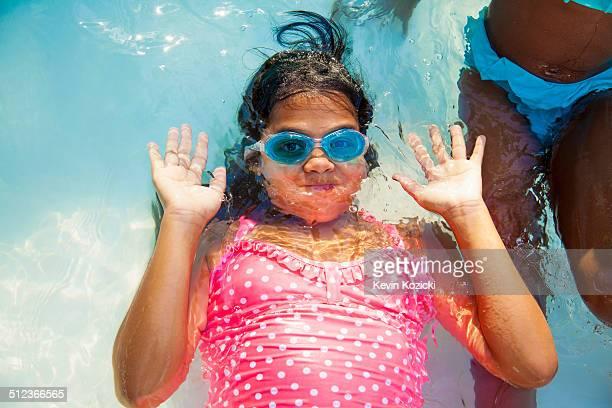 Girl in swimming goggles underwater in garden paddling pool