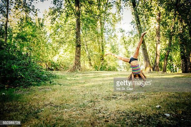 Girl in swimsuit doing cartwheel in forest
