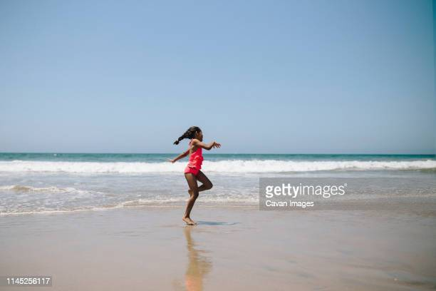 girl in swimwear dancing at beach against clear sky during sunny day - swimwear stock pictures, royalty-free photos & images