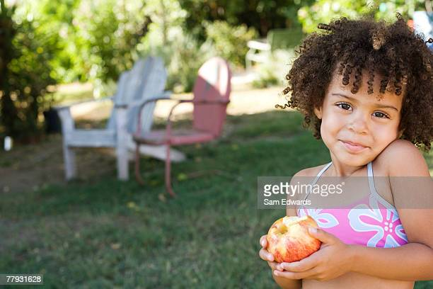 girl in swimwear holding apple in yard - kid girl eating apple stock photos and pictures