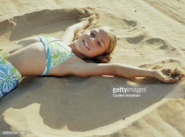 girl (6-8) in swimwear making sand angel on beach, smiling, portrait - little girl laying on the beach stock photos and pictures
