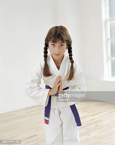 Girl (7-9) in Tae Kwan Do uniform bowing, portrait