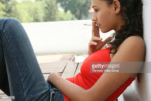 Girl in teenage smoking cigarette in New Delhi India