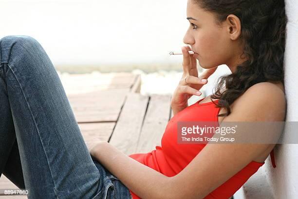 Girl in teenage smoking cigarette in New Delhi India