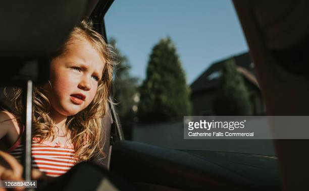 girl in the back seat of a sunny car, looking through the open window - window stock pictures, royalty-free photos & images