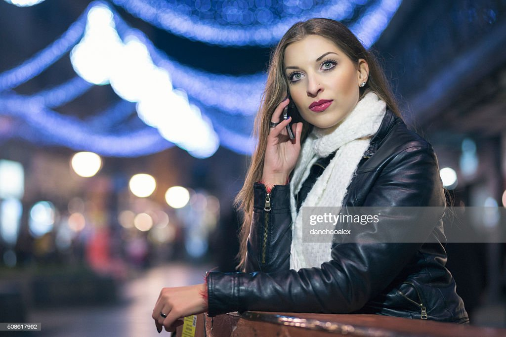 Girl in the city at night using smart phone : Stock Photo