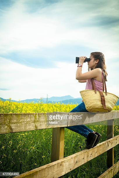 girl in the country using binoculars - guess jeans stock photos and pictures