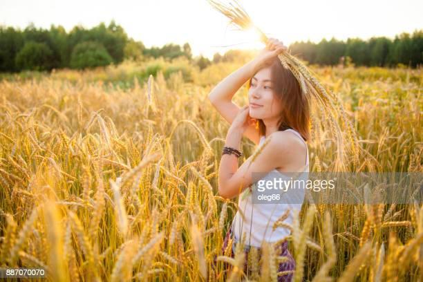 chica en el campo entre las espigas de trigo