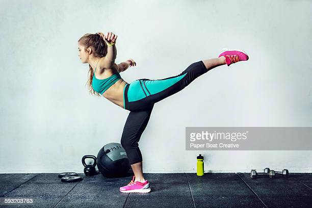 Girl in the gym stretching her legs and back