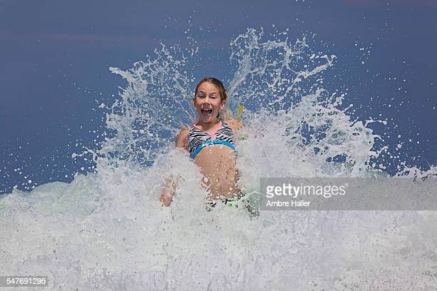 Girl in the ocean with a wave crashing over her