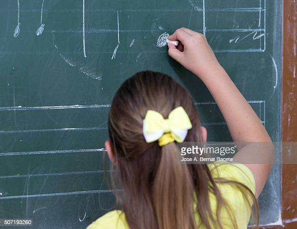 Girl in the school writing notes of music in the slate