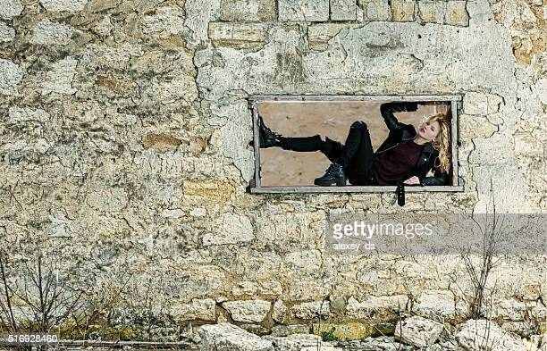 Girl in the window frame of ruined building