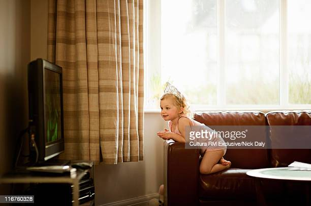 Girl in tiara watching television
