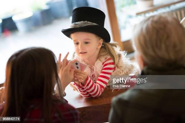 girl (4-5) in top hat, performing magic trick for family - zaubertrick stock-fotos und bilder
