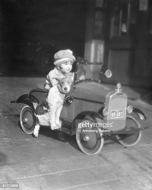 Girl in toy pedal car with dog sitting on running board.