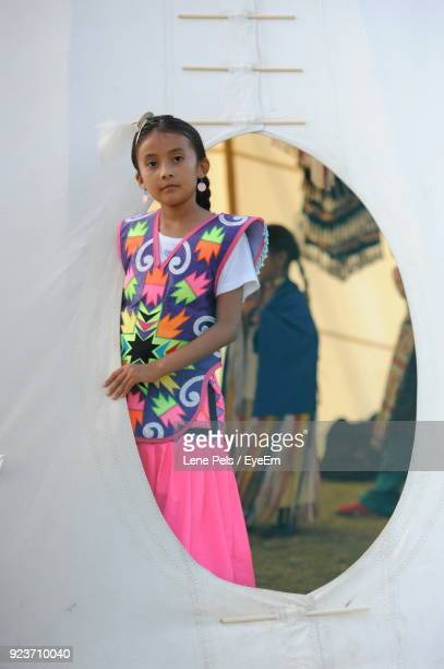 girl in traditional clothing standing by fabric - lene pels stockfoto's en -beelden