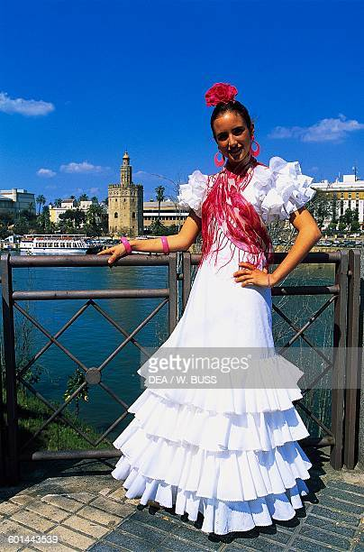 Girl in traditional costume during the Feria de Abril with the Gold Tower in the background 12th century Seville Andalusia Spain