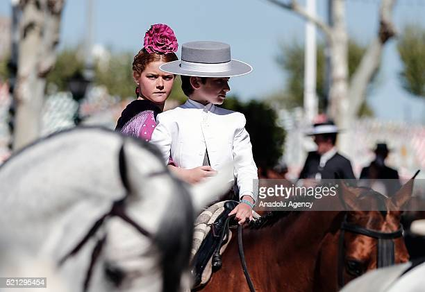 A girl in traditional flamenco dress and with flowers on her head and a boy are seen during horseback parade at the 'Feria de Abril 2016' the...