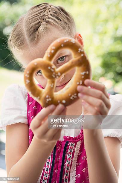 Girl in traditional Oktoberfest dress, holding pretzel