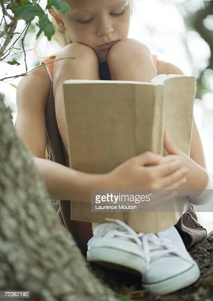 Girl in tree reading book