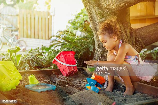 Girl in tutu playing in sandbox in yard