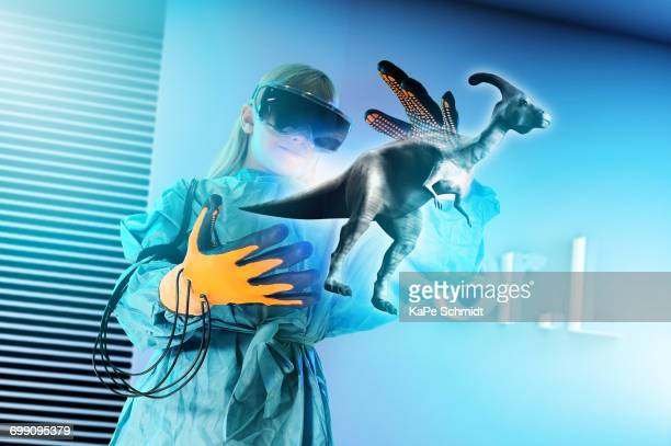 Girl in virtual reality headset interacting with digital floating dinosaur