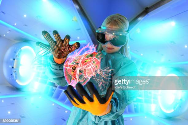Girl in virtual reality headset interacting with digital floating human heart