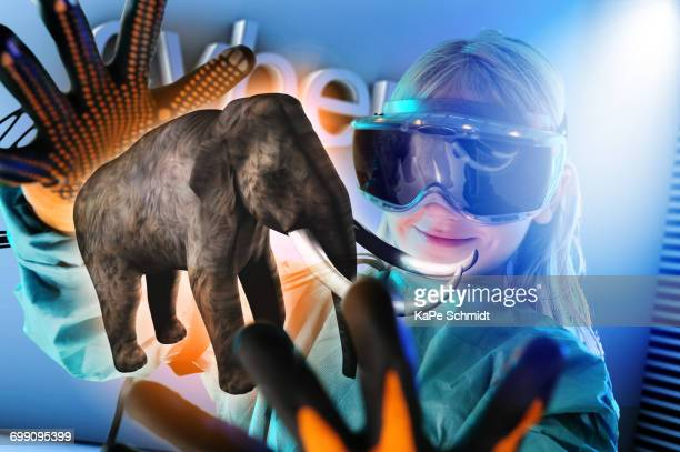 Girl in virtual reality headset interacting with digital floating elephant