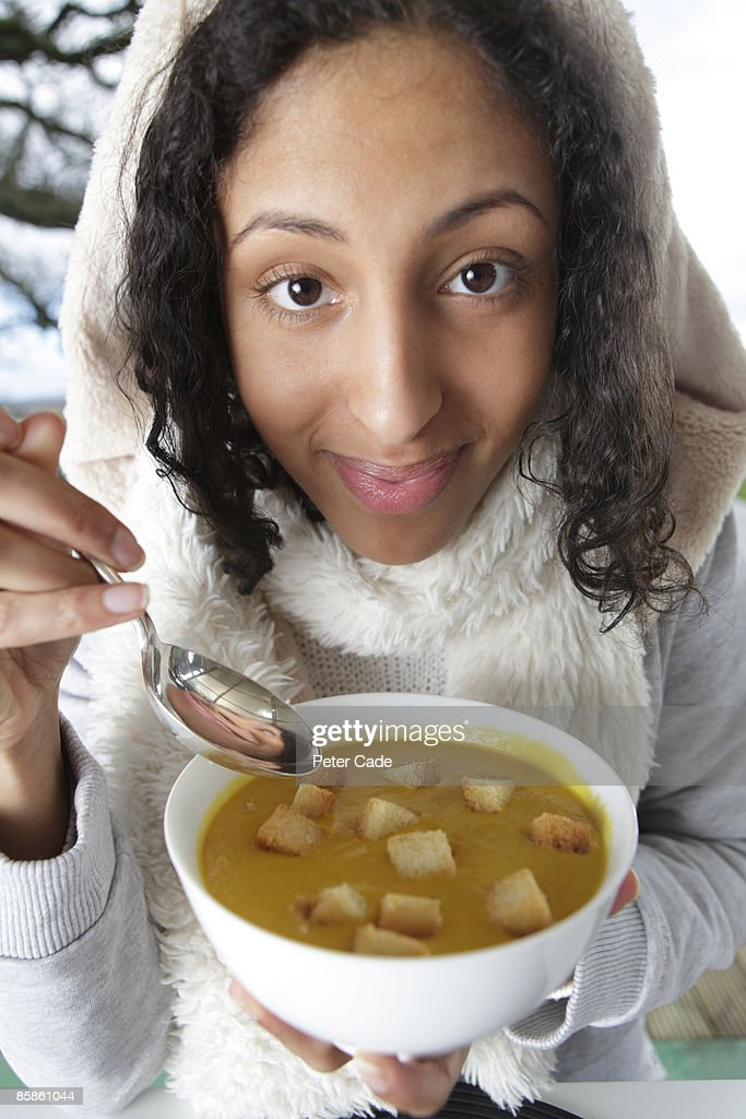 Girl in warm clothes eating soup : Stock-Foto