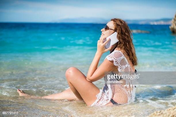 Girl in water making call on cell phone
