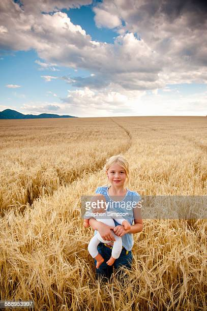 girl in wheat field with generic doll