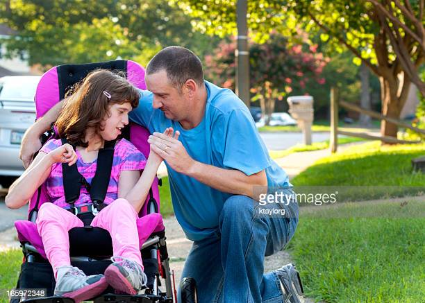 Girl in wheelchair holds Daddy's hand