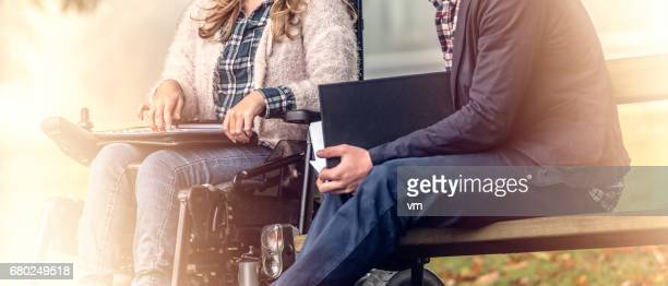 Girl in wheelchair studying with her classmate