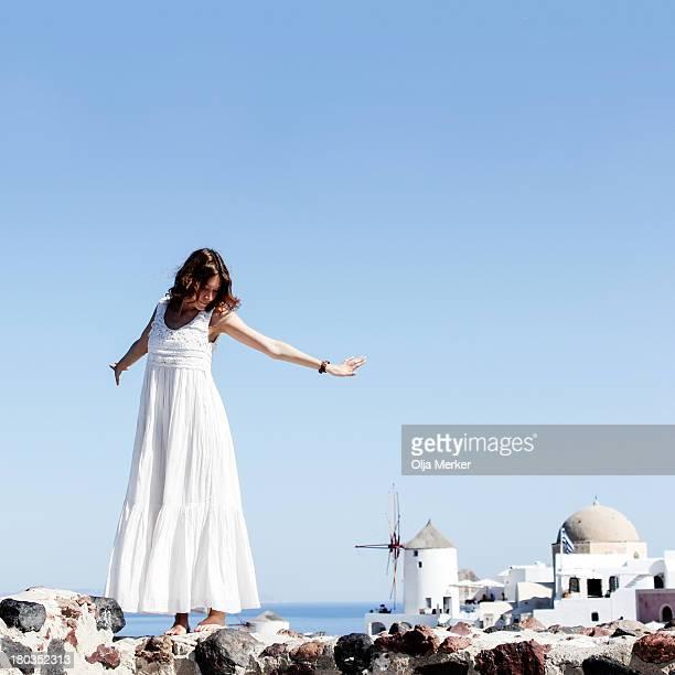 Girl in white dress against an island Santorini