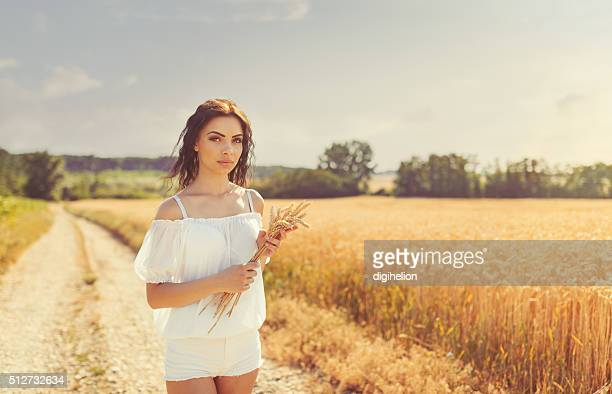 girl in white dress standing on lane near wheat field - curvy girls stock photos and pictures