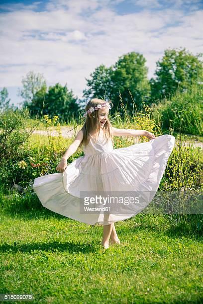 Girl in white summer dress on meadow